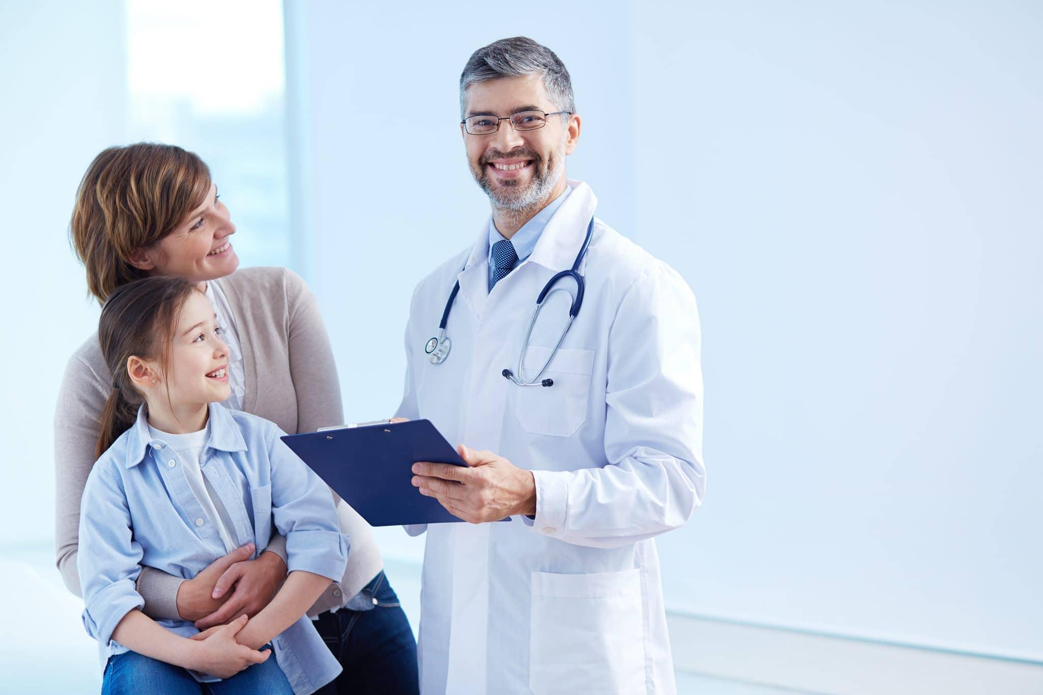 Kinderarzt mit Patientin in Kinderarztpraxis